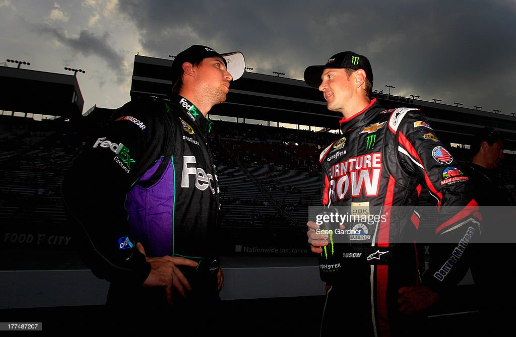 Denny Hamlin, driver of the #11 FedEx Ground Toyota, talks with Kurt Busch, driver of the #78 Furniture Row / Sealy Chevrolet, on the grid during qualifying for the NASCAR Sprint Cup Series IRWIN Tools Night Race at Bristol Motor Speedway on August 23, 2013 in Bristol, Tennessee.