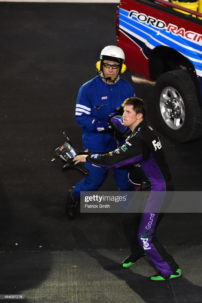 <a gi-track='captionPersonalityLinkClicked' href=/galleries/search?phrase=Denny+Hamlin&family=editorial&specificpeople=504674 ng-click='$event.stopPropagation()'>Denny Hamlin</a>, driver of the #11 FedEx Ground Toyota, throws his hans device at Kevin Harvick (not pictured), driver of the #4 Jimmy John's Chevrolet, after an on-track incident during the NASCAR Sprint Cup Series Irwin Tools Night Race at Bristol Motor Speedway on August 23, 2014 in Bristol, Tennessee.