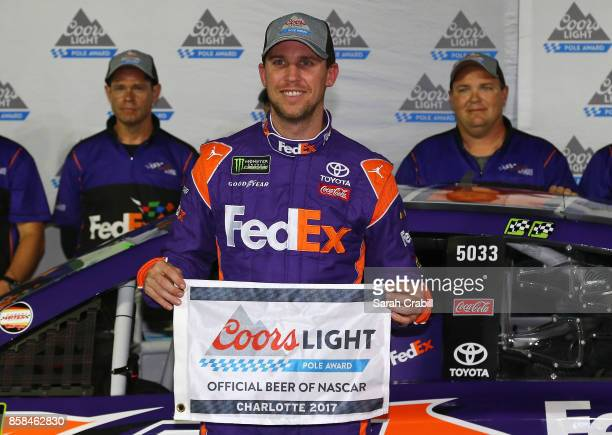 Denny Hamlin driver of the FedEx Office Toyota and his team pose with the Coors Light Pole Award after qualifying in the pole position for the...