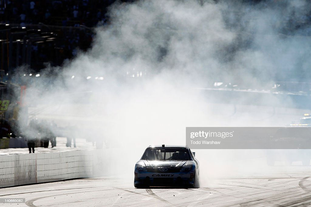 Denny Hamlin driver of the FedEx Office Toyota celebrates with a burn out after winning the NASCAR Sprint Cup Series SUBWAY Fresh Fit 500 at Phoenix...