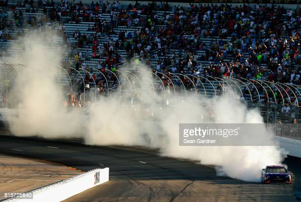 Denny Hamlin driver of the FedEx Office Toyota celebrates with a burnout after winning the Monster Energy NASCAR Cup Series Overton's 301 at New...