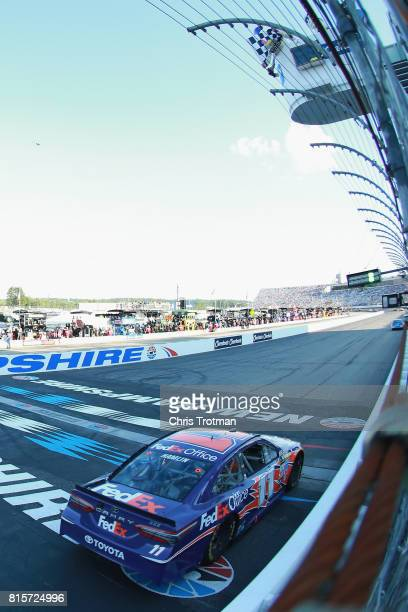 Denny Hamlin driver of the FedEx Office Toyota crosses the finish line to win the Monster Energy NASCAR Cup Series Overton's 301 at New Hampshire...