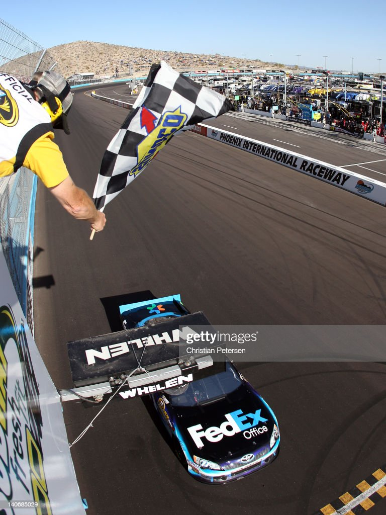 Denny Hamlin driver of the FedEx Office Toyota crosses the finishline to win the NASCAR Sprint Cup Series SUBWAY Fresh Fit 500 at Phoenix...