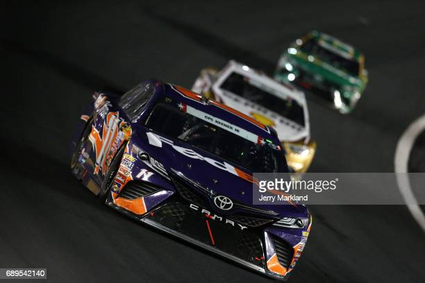 Denny Hamlin driver of the FedEx Office Toyota leads Joey Logano driver of the Shell Pennzoil Ford and Daniel Suarez driver of the Subway Toyota...