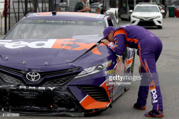 Denny Hamlin driver of the FedEx Office Toyota looks at the damage to his car after hitting the front stretch wall during practice for the Monster...