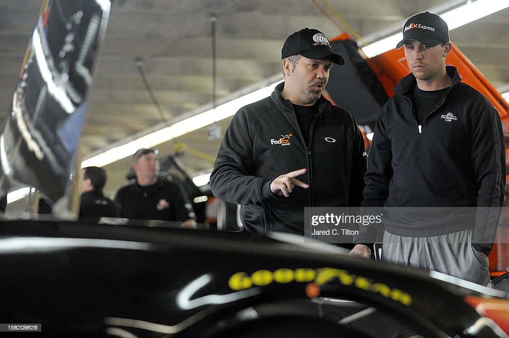 Denny Hamlin (R), driver of the #11 FedEx Toyota, speaks with crew chief, Darian Grubb during testing at Charlotte Motor Speedway on December 11, 2012 in Concord, North Carolina.