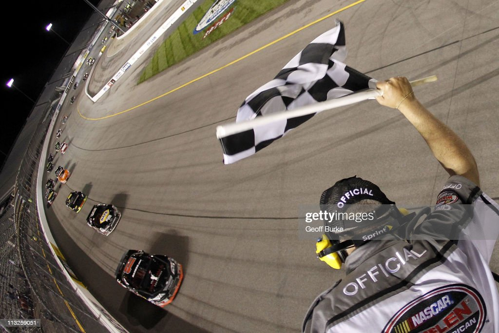 Denny Hamlin driver of the FedEx/Denny Hamlin Foundation Toyota takes the checkered flag ahead of Michael Waltrip driver of the Aaron's Toyota to win...