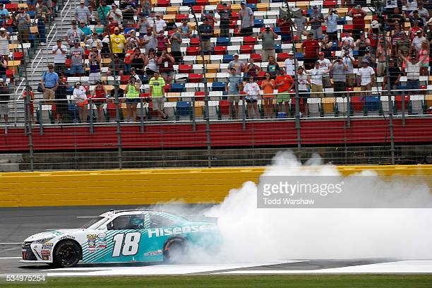 Denny Hamlin driver of the Hisense USA Toyota celebrates with a burnout after winning the NASCAR XFINITY Series Hisense 300 at Charlotte Motor...