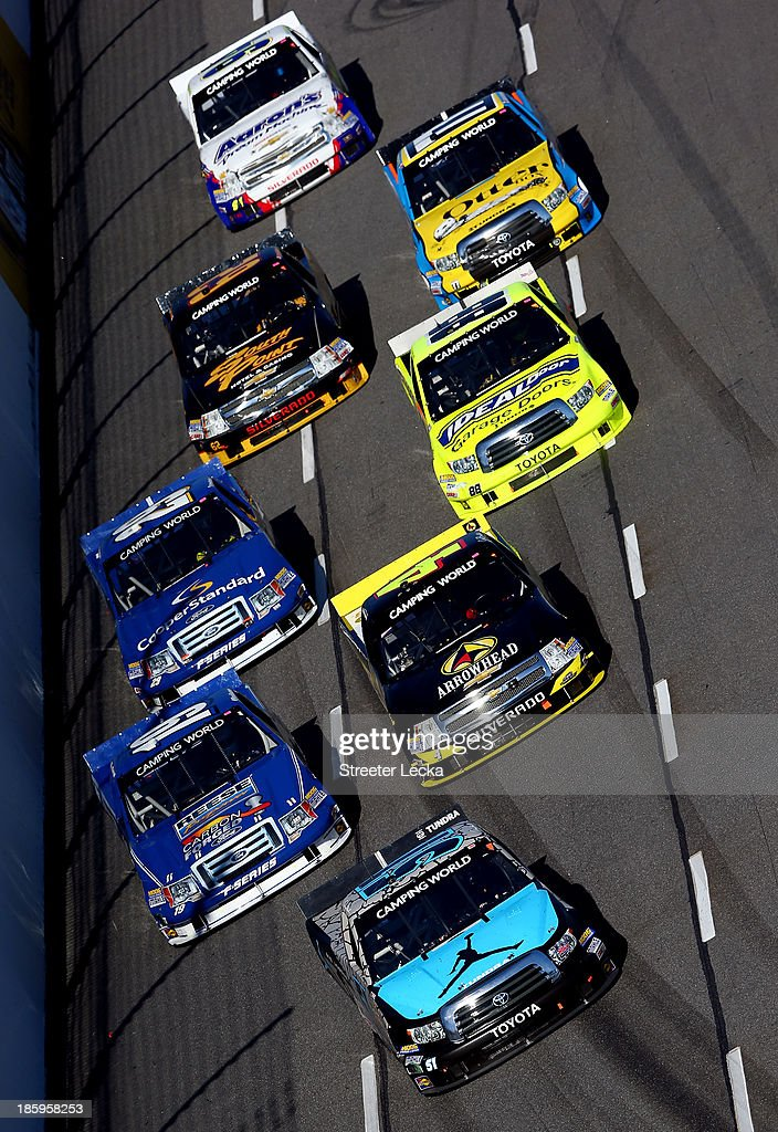 <a gi-track='captionPersonalityLinkClicked' href=/galleries/search?phrase=Denny+Hamlin&family=editorial&specificpeople=504674 ng-click='$event.stopPropagation()'>Denny Hamlin</a>, driver of the #51 Jordan Brand Toyota, leads a pack of trucks during the NASCAR Camping World Truck Series Kroger 200 at Martinsville Speedway on October 26, 2013 in Martinsville, Virginia.