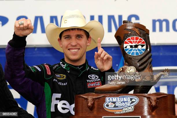 Denny Hamlin driver of the of the FedEx Ground Toyota celebrates with the trophy in victory lane after he won the NASCAR Sprint Cup Series Samsung...