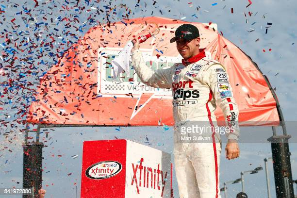 Denny Hamlin driver of the Sport Clips Toyota celebrates in Victory Lane after winning the NASCAR XFINITY Series Sports Clips Haircuts VFW 200 at...