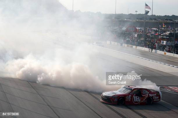 Denny Hamlin driver of the Sport Clips Toyota celebrates with a burnout after winning the NASCAR XFINITY Series Sports Clips Haircuts VFW 200 at...