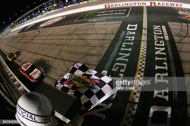 Denny Hamlin driver of the Sport Clips Toyota crosses the finish line to win the Monster Energy NASCAR Cup Series Bojangles' Southern 500 at...