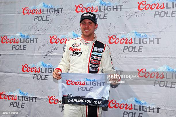 Denny Hamlin driver of the Sport Clips Toyota poses with the Coors Light Pole Award after qualifying for the pole for the NASCAR XFINITY Series VFW...