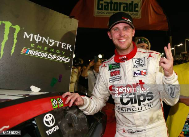 Denny Hamlin driver of the Sport Clips Toyota poses with the winner's decal on his car in Victory Lane after winning the Monster Energy NASCAR Cup...