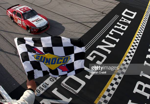 Denny Hamlin driver of the Sport Clips Toyota takes the checkered flag to win the NASCAR XFINITY Series Sports Clips Haircuts VFW 200 at Darlington...
