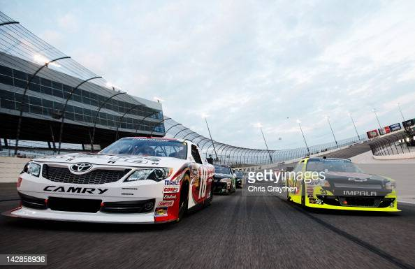 Denny Hamlin driver of the SportClips Toyota and Paul Menard driver of the Menards/Rheem Chevrolet take a pace lap before the start of the NASCAR...