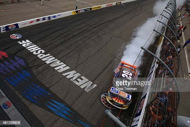 Denny Hamlin driver of the Sun Energy 1 Toyota celebrates with a burnout after winning the NASCAR XFINITY Series Lakes Region 200 at New Hampshire...