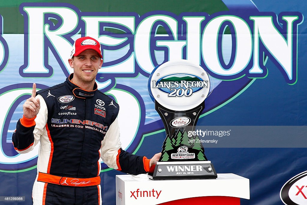 Denny Hamlin, driver of the #20 Sun Energy 1 Toyota, poses with the trophy in Victory Lane after winning the NASCAR XFINITY Series Lakes Region 200 at New Hampshire Motor Speedway on July 18, 2015 in Loudon, New Hampshire.
