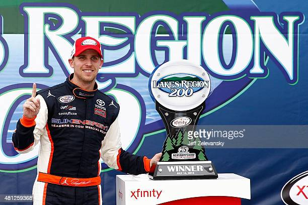 Denny Hamlin driver of the Sun Energy 1 Toyota poses with the trophy in Victory Lane after winning the NASCAR XFINITY Series Lakes Region 200 at New...