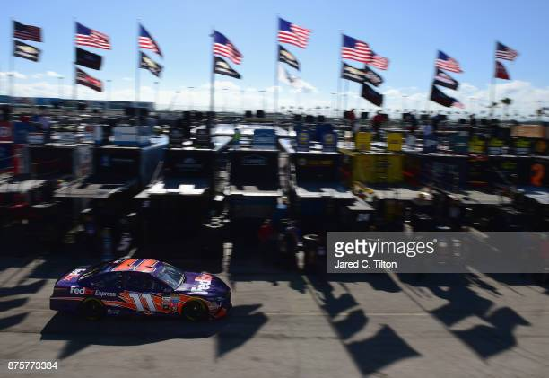 Denny Hamlin drives the FedEx Express Toyota through the garage area during practice for the Monster Energy NASCAR Cup Series Championship Ford...
