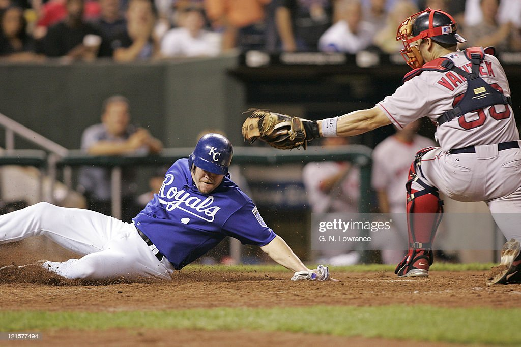 Denny Hocking of the Kansas City Royals slides in ahead of the tag by <a gi-track='captionPersonalityLinkClicked' href=/galleries/search?phrase=Jason+Varitek&family=editorial&specificpeople=171480 ng-click='$event.stopPropagation()'>Jason Varitek</a> of the Boston Red Sox at Kauffman Stadium in Kansas City, Mo. on August 25, 2005. The Royals won 7-4.