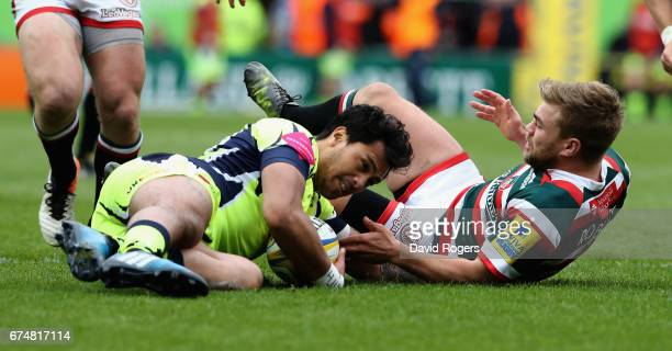 Denny Solomona of Sale is tackled by Jack Roberts during the Aviva Premiership match between Leicester Tigers and Sale Sharks at Welford Road on...
