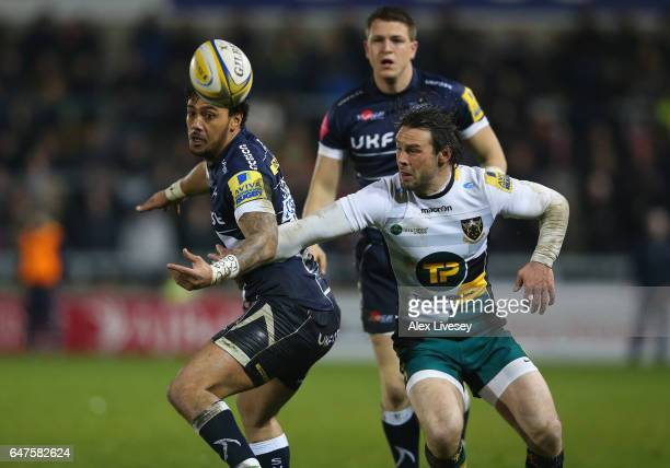 Denny Solomona of Sale Sharks and Ben Foden of Northampton Saints battle for a loose ball during the Aviva Premiership match between Sale Sharks and...