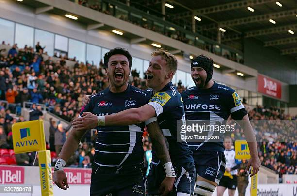 Denny Solomona of Sale Sharks celebrates scoring a try with Mike Haley of Sale Sharks and Josh Beaumont of Sale Sharks during the Aviva Premiership...