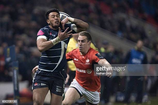 Denny Solomona of Sale Sharks fumbles the ball under pressure from Chris Wyles of Saracens in action during the European Rugby Champions Cup match...