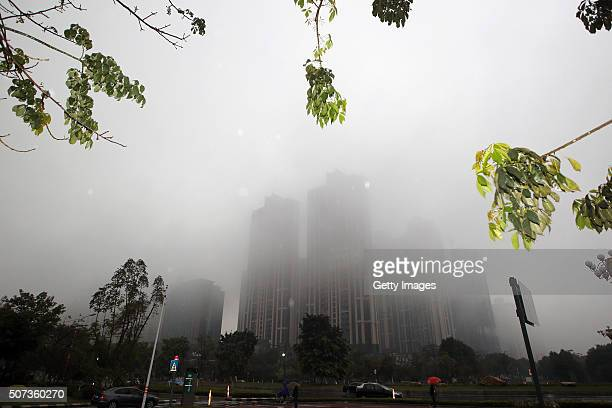 Dense fog envelops buildings on January 28 2016 in Foshan Guangdong Province of China Many parts in south China encountered heavy rainfall and dense...