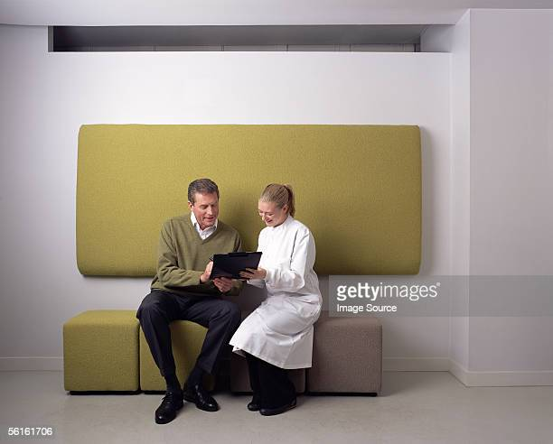 Dental assistant and patient in waiting room