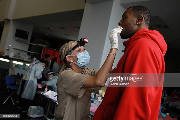Dental assistant Stefanie Brule helps a patient during the Bridges to Health medical and dental clinic at the Oco Coliseum on April 25 2014 in...
