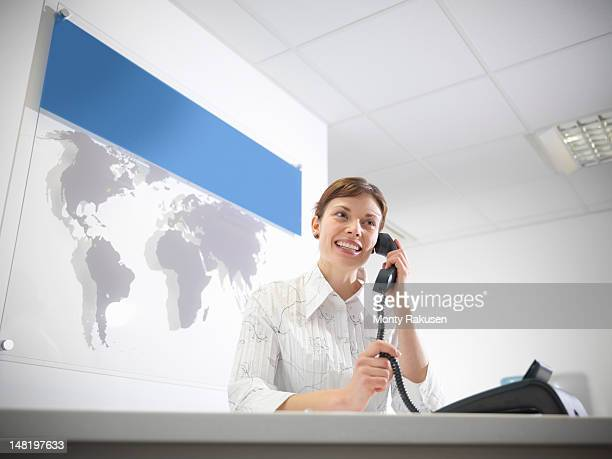 Dental receptionist taking telephone call at reception desk, smiling