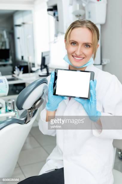 Dental student holding blank digital tablet