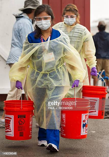 Dental students carry water to use at a dental tool cleaning station during the nonprofit Remote Area Medical clinic held at the county fairgrounds...