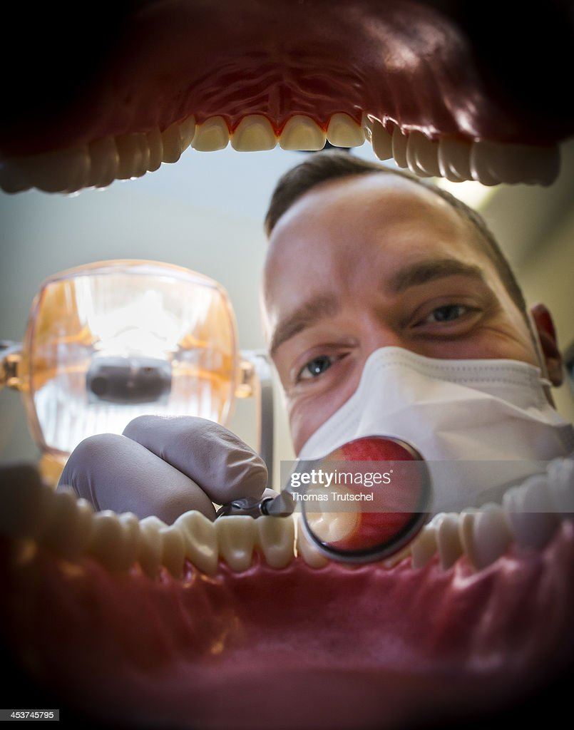 Dental treatment at a dental clinic on November 04, 2013, in Berlin, Germany. A dentist is inspecting a set of teeth. Photo by Thomas Trutschel/Photothek via Getty Images)