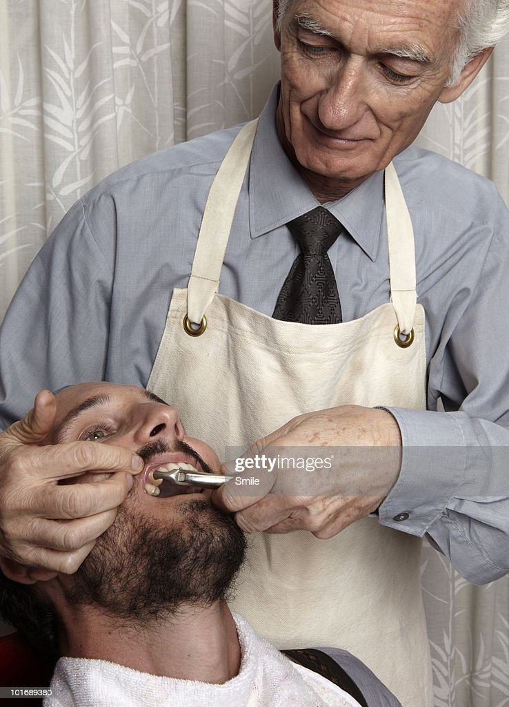 Dentist about to pull patient's tooth : Stock Photo