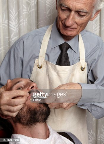 Dentist about to pull patient's tooth