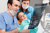 Dentist and patient looking at tooth x-ray