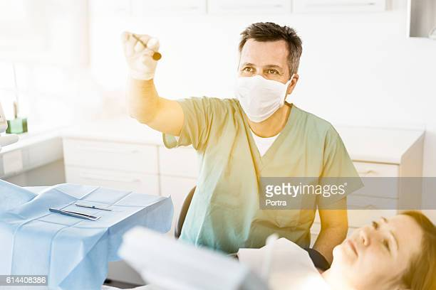 Dentist and patient looking away in dental clinic