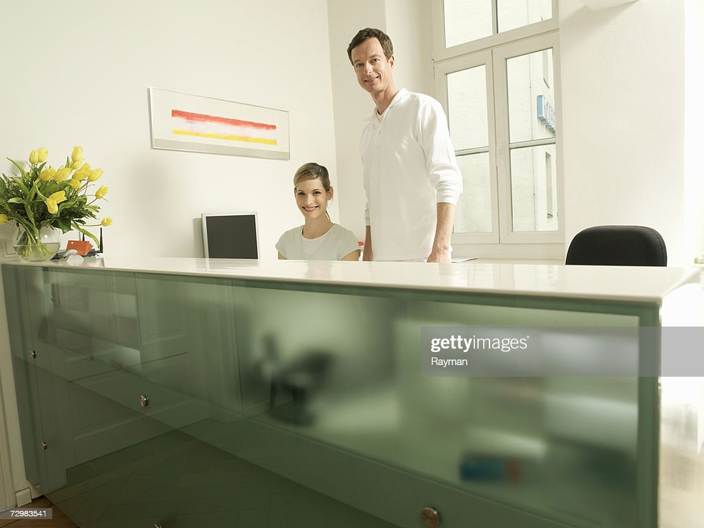 Dentist and receptionist behind desk, in office : Stock Photo