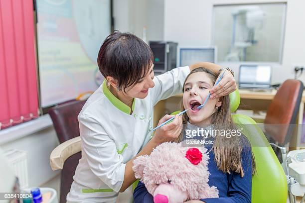 Dentist examining girls teeth