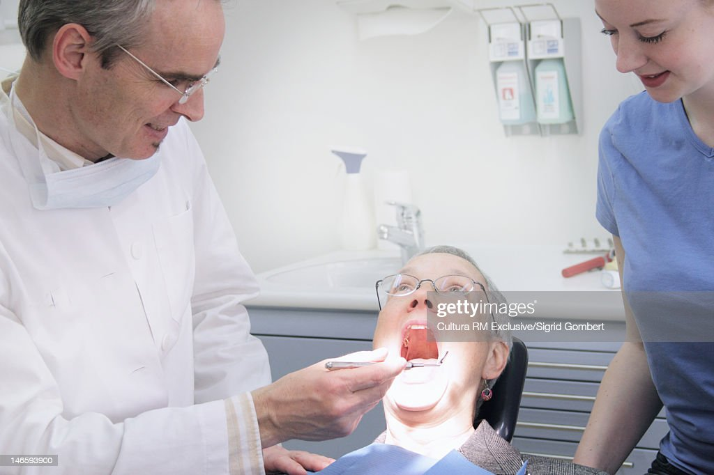 Dentist examining patients mouth : Stock Photo