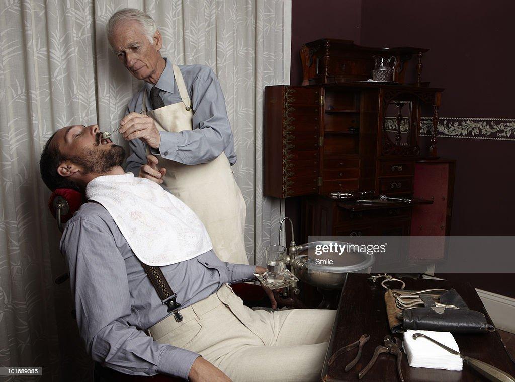 Dentist examining patient's teeth : Stock Photo