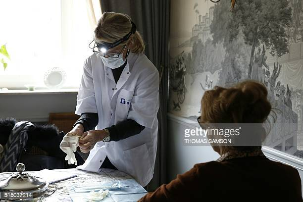 A dentist from the 'Incisiv' network prepares her tools before dispensing dental homecare to an old woman in Paris on March 10 2016 'Incisiv' is a...