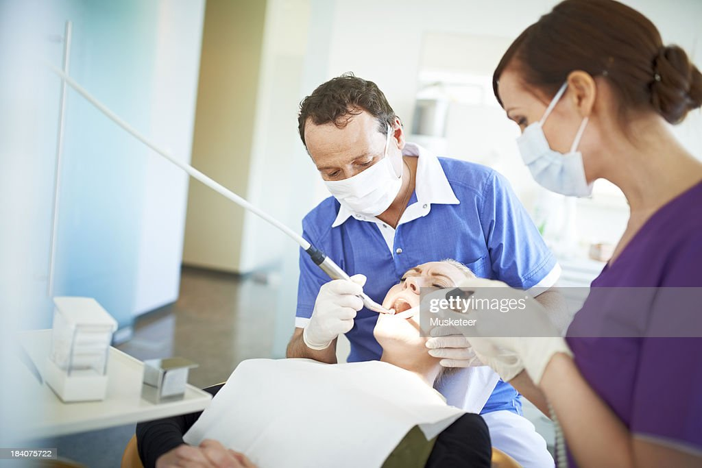 Dentist operating on a patient in pain : Stock Photo