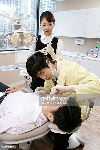 Dentist operating patient in dentist office