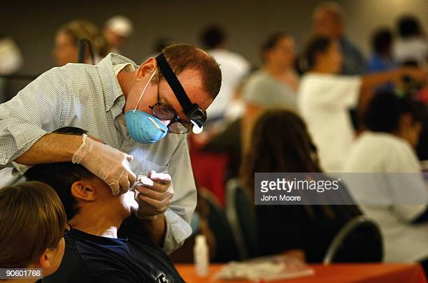 Dentist Paul Beer checks a patient's teeth at a free dental clinic September 11 2009 in Brighton Colorado The third annual Colorado Mission of Mercy...