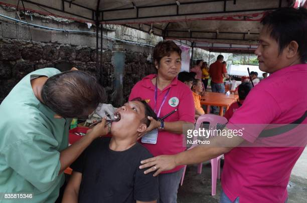 A dentist performs a tooth extraction to a patient during a medical mission at a village in Quezon City east of Manila Philippines on Sunday August...